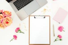 Ordenador portátil, tablero, flores de las rosas y accesorios en el fondo blanco Endecha plana Visión superior Concepto de la ofi Fotos de archivo