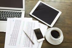 Ordenador portátil, tableta, smartphone con los documentos financieros en la tabla de madera Imagen de archivo libre de regalías
