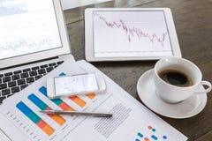Ordenador portátil, tableta, smartphone con los documentos financieros en la tabla de madera foto de archivo