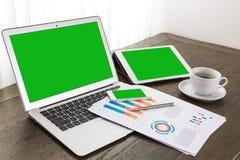 Ordenador portátil, tableta, smartphone con los documentos financieros financieros Fotografía de archivo libre de regalías