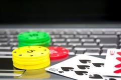 Ordenador portátil, tarjetas del póker y fichas de póker Fotografía de archivo