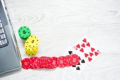 Ordenador portátil, tarjetas del póker y fichas de póker Fotos de archivo libres de regalías
