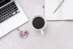 Ordenador portátil, taza de café y cuaderno situado en fondo de la alfombra Foto de archivo