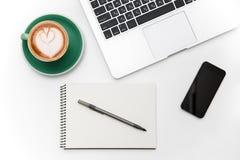 Ordenador portátil, teléfono móvil de la pantalla en blanco, taza de café, libreta y pluma Foto de archivo