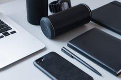 Ordenador portátil, teléfono negro, cuaderno negro y pluma negra con el altavoz negro en la tabla blanca, primer, oficina, trabaj imágenes de archivo libres de regalías