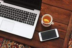 Ordenador portátil, teléfono y té en fondo de madera fotografía de archivo libre de regalías