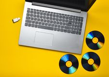 Ordenador portátil, unidades de CD, memoria USB en un fondo amarillo Medios digitales modernos y anticuados Imagen de archivo