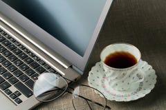 Ordenador portátil, vidrios y una taza de té Fotos de archivo libres de regalías
