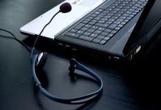 Ordenador portátil y auricular con el micrófono Fotos de archivo libres de regalías