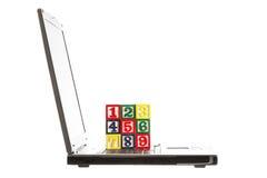 Ordenador portátil y bloques de madera con números aislados en blanco Foto de archivo