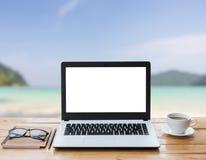 Ordenador portátil y café en el espacio de trabajo de madera y la playa imagenes de archivo