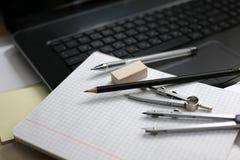 Ordenador portátil y compás en un cuaderno Fotografía de archivo