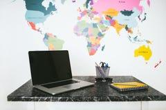 Ordenador portátil y cuaderno en la tabla fotografía de archivo