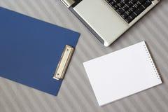 Ordenador portátil y cuaderno en una tela escocesa rayada suave Foto de archivo libre de regalías