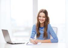 Ordenador portátil y cuaderno sonrientes del adolescente Imagen de archivo libre de regalías