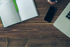 Ordenador portátil y diario en el escritorio Fotos de archivo libres de regalías