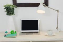 Ordenador portátil y diversos accesorios de la oficina en la tabla Imagenes de archivo