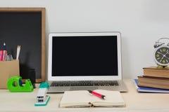 Ordenador portátil y diversos accesorios de la oficina en la tabla Foto de archivo