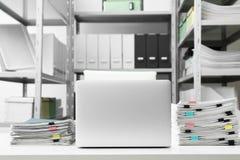 Ordenador portátil y documentos en el escritorio foto de archivo libre de regalías