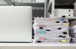 Ordenador portátil y documentos en el escritorio imagenes de archivo