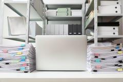 Ordenador portátil y documentos en el escritorio fotos de archivo