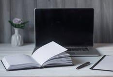 Ordenador portátil y documentos en el lugar de trabajo Foto de archivo libre de regalías