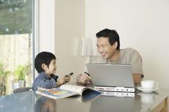 Ordenador portátil y libro de colorear de And Son With del padre en la tabla Fotos de archivo libres de regalías