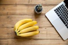 Ordenador portátil y manojo de plátanos maduros frescos en la sobremesa de madera Fotos de archivo libres de regalías