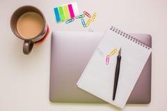 Ordenador portátil y materiales de oficina en la tabla blanca Foto de archivo libre de regalías
