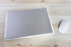 Ordenador portátil y ratón en la tabla de madera imagen de archivo libre de regalías