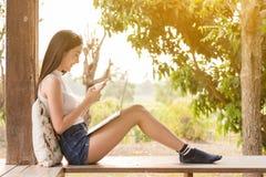 Ordenador portátil y smartphone asiáticos hermosos del uso del adolescente de la mujer con su Fotografía de archivo