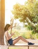 Ordenador portátil y smartphone asiáticos hermosos del uso del adolescente de la mujer con su Imagen de archivo libre de regalías