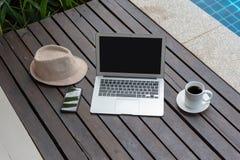 Ordenador portátil y sombrero en la piscina fotos de archivo libres de regalías