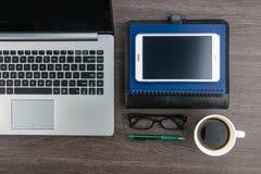 Ordenador portátil y tableta con el cuaderno y pluma en el escritorio Imagenes de archivo