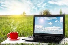 Ordenador portátil y taza de café caliente en la tabla, oficina al aire libre El viajar en aeroplano concepto del recorrido Ideas Fotos de archivo