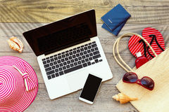 Ordenador portátil y teléfono elegante con los accesorios de la playa en el tablero de madera imagenes de archivo