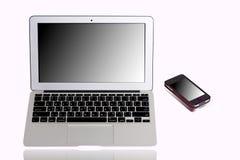 Ordenador portátil y teléfono móvil, monitor del espejo Imagen de archivo