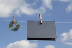Ordenador portátil y un CD en cuerda para tender la ropa Fotografía de archivo libre de regalías
