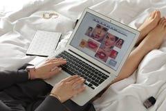 Ordenador port?til de la tenencia de la mujer con el sitio abierto del blogger de la belleza en cama imagen de archivo