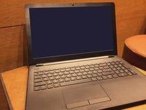 Ordenador port?til en la tabla, pantalla vac?a foto de archivo libre de regalías
