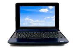 Ordenador portátil con el papel pintado azul del cielo nublado Imágenes de archivo libres de regalías