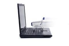 Ordenador portátil con el pequeño carro de la compra Fotos de archivo libres de regalías