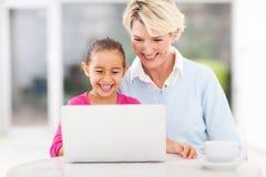 Ordenador portátil de la abuelita de la niña Imágenes de archivo libres de regalías