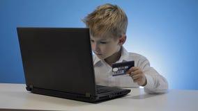 Ordenador portátil del uso del niño pequeño y tarjeta de crédito lindos almacen de metraje de vídeo