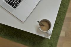Ordenador portátil MacBook Pro que miente en la tabla cerca de la taza de o de café Foto de archivo