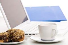 Ordenador portátil, tortas y taza de café Imagenes de archivo