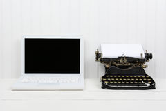 Ordenador portátil y máquina de escribir modernos de la antigüedad Imágenes de archivo libres de regalías