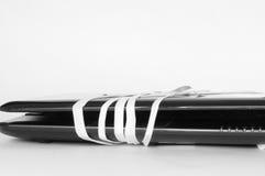 Ordenador roto con una cinta blanca Foto de archivo