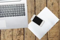 Ordenador, smartphone y documento sobre la tabla de madera Imagenes de archivo