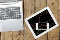 Ordenador, smartphone y tableta con el gráfico en la tabla de madera Imagenes de archivo